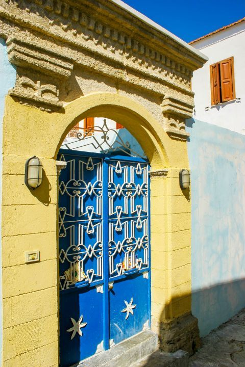 Koskinou: The yellow entrance of a house and its blue-colored door.