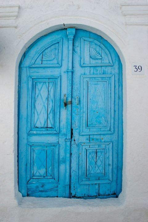 Koskinou: A whitewashed house with a wooden door in light blue color.