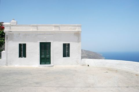 Chora: A white-colored building with green shutters and door.
