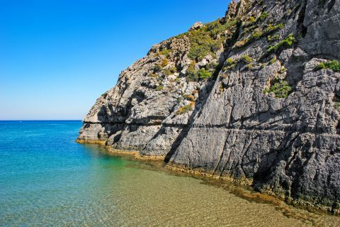 Tsambika: A big cliff, emerging from the sea on Tsambika beach.