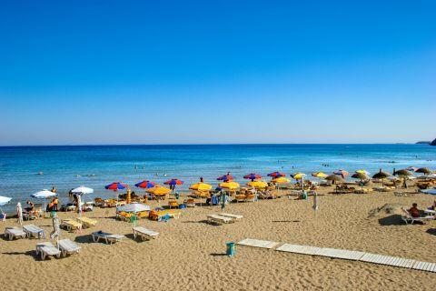 Tsambika: Colorful umbrellas and sun loungers, on the sea front of Tsambika beach.