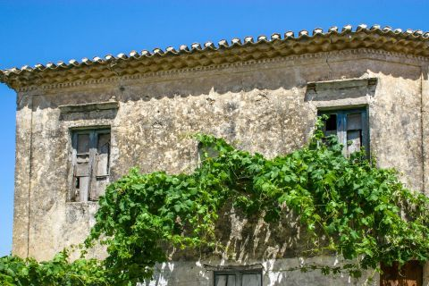 Volimes: A partly ruined building with some trees outside it,.