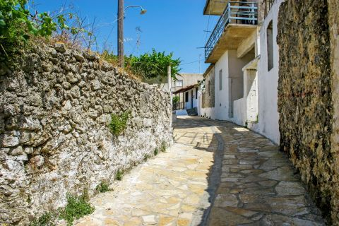 Volimes: A narrow path with stone built walls and paved street.