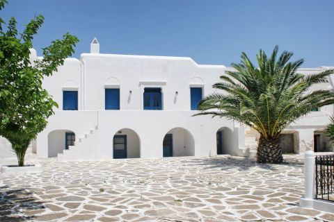 Chora: A whitewashed house with blue colored windows and trees