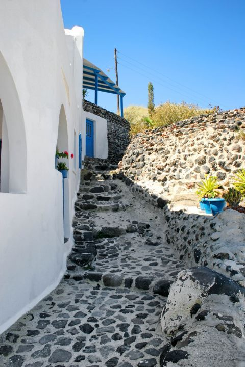 A rock-paved path outside a Cycladic house