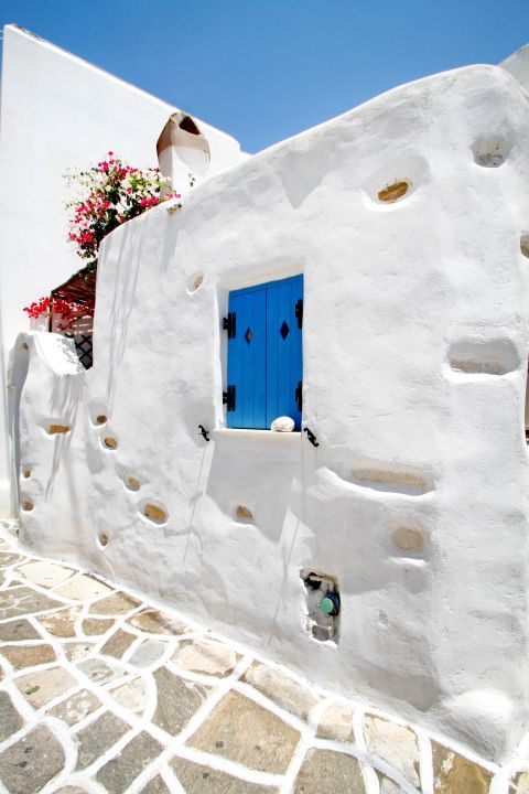 Prodromos: A whitewashed building with a blue-colored window