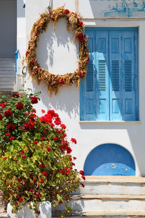 Galini: A whitewashed house with blue-colored windows and beautiful flowers