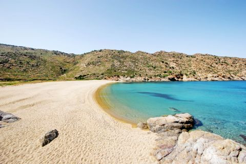 Papa: A sandy beach with hills and blue waters
