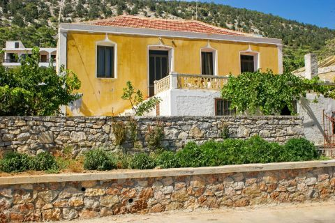 Monolithos: A yellow building, surrounded by small, stone built walls and lush vegetation.