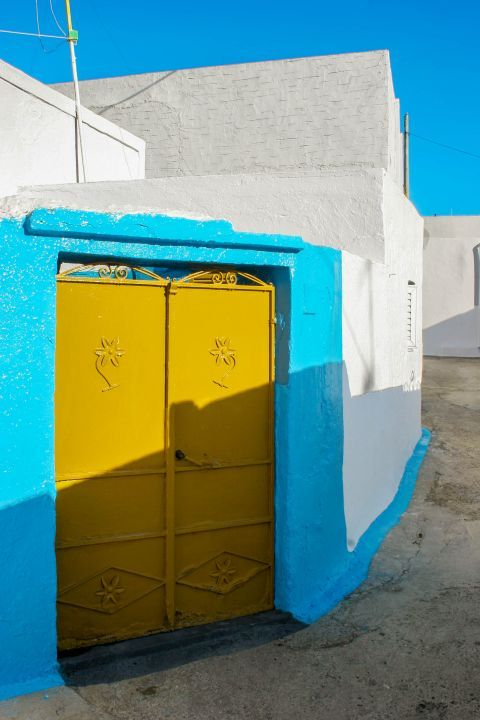 Archangelos: A whitewashed house with blue colored details and a yellow door.