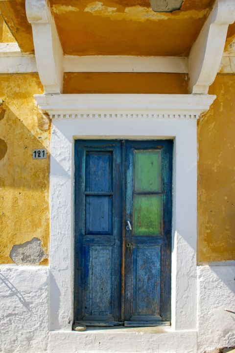 Siana: The blue colored, wooden door of an old, neoclassical mansion.