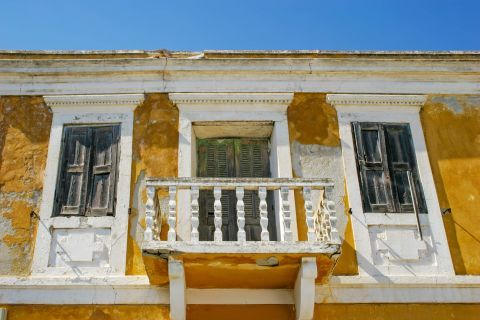 Siana: An old neoclassical building with wooden shutters and a small balcony.