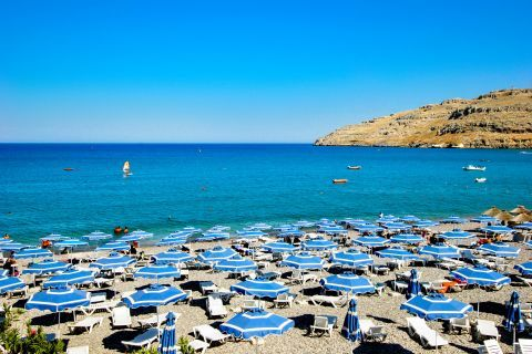 Vlicha: Umbrellas and sun loungers on the seafront of Vlicha beach.